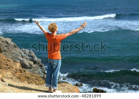 Man stretching arms in front of the sea - stock photo