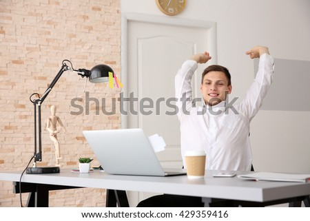 Man stretching his arms at office
