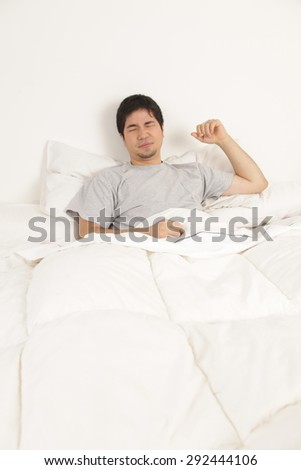 Man stretching in his bed