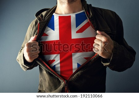 Man stretching jacket to reveal shirt with Great Britain flag printed. Concept of patriotism and national team supporting. - stock photo