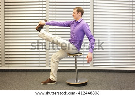 man stretching leg,sitting on pneumatic stool in office - healthy lifestyle, profile view  - stock photo