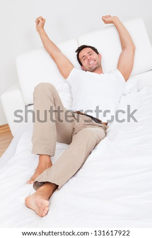 Man Stretching On Bed While Waking Up, Indoors - stock photo