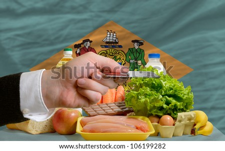 man stretching out credit card to buy food in front of complete wavy american state flag of delaware - stock photo