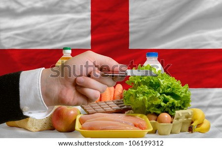 man stretching out credit card to buy food in front of complete wavy national flag of england