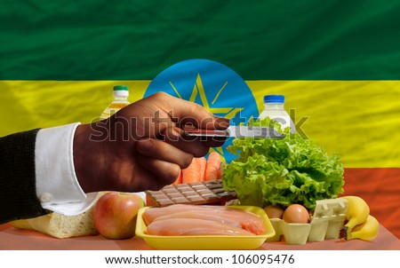 man stretching out credit card to buy food in front of complete wavy national flag of ethiopia - stock photo