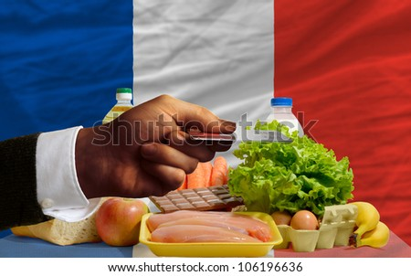 man stretching out credit card to buy food in front of complete wavy national flag of france - stock photo