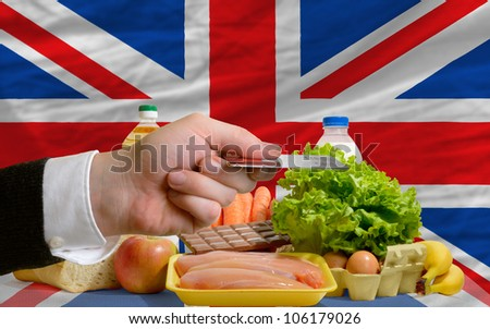 man stretching out credit card to buy food in front of complete wavy national flag of great britain - stock photo