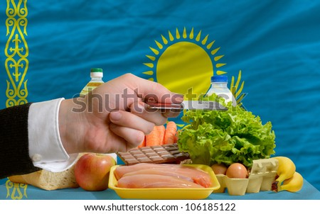 man stretching out credit card to buy food in front of complete wavy national flag of kazakhstan - stock photo