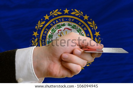 man stretching out credit card to buy goods in front of complete wavy national flag of american state of new hampshire