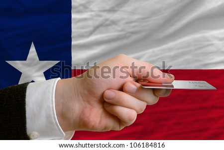 man stretching out credit card to buy goods in front of complete wavy national flag of american state of texas - stock photo