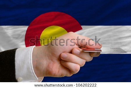 man stretching out credit card to buy goods in front of complete wavy national flag of american state of colorado - stock photo