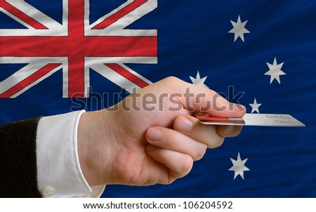 man stretching out credit card to buy goods in front of complete wavy national flag of australia - stock photo