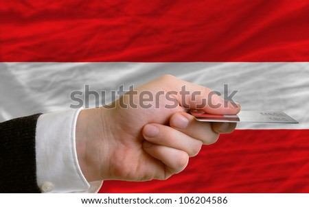 man stretching out credit card to buy goods in front of complete wavy national flag of austria - stock photo