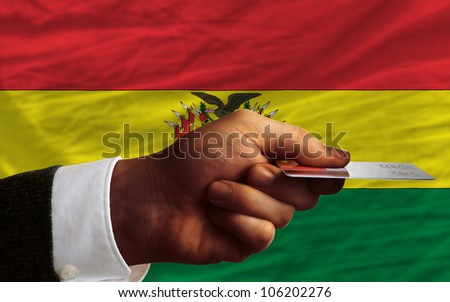 man stretching out credit card to buy goods in front of complete wavy national flag of bolivia - stock photo