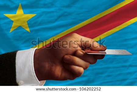 man stretching out credit card to buy goods in front of complete wavy national flag of congo - stock photo