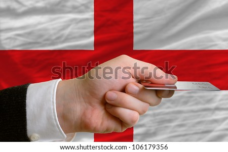 man stretching out credit card to buy goods in front of complete wavy national flag of england