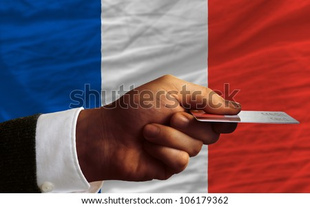 man stretching out credit card to buy goods in front of complete wavy national flag of france - stock photo