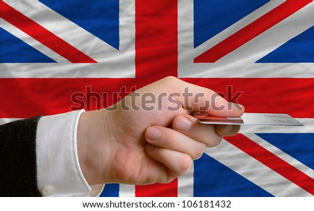 man stretching out credit card to buy goods in front of complete wavy national flag of great britain - stock photo