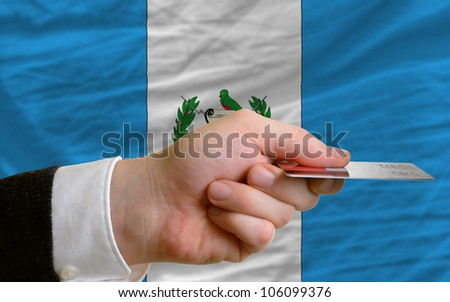 man stretching out credit card to buy goods in front of complete wavy national flag of guatemala - stock photo