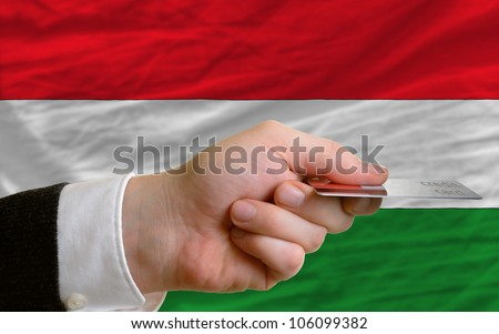 man stretching out credit card to buy goods in front of complete wavy national flag of hungary - stock photo