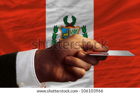 man stretching out credit card to buy goods in front of complete wavy national flag of peru - stock photo