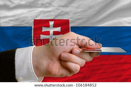 man stretching out credit card to buy goods in front of complete wavy national flag of slovakia - stock photo