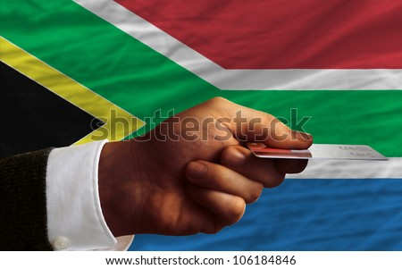 man stretching out credit card to buy goods in front of complete wavy national flag of south africa - stock photo