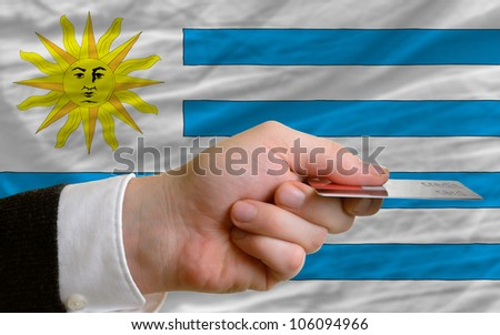man stretching out credit card to buy goods in front of complete wavy national flag of uruguay