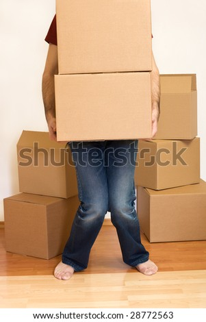 Man struggling lifting cardboard boxes - moving concept - stock photo