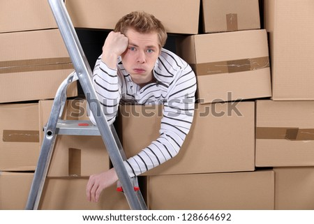 Man stuck behind stacks of cardboard boxes - stock photo