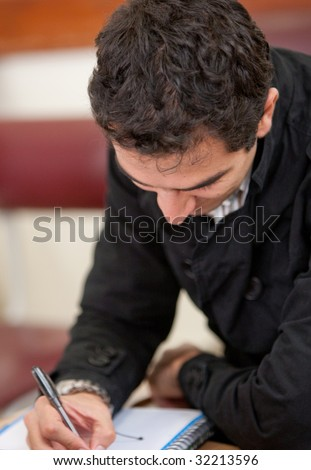 Man studying and writting on his notebook