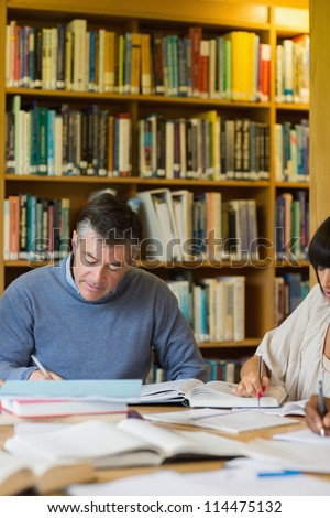 Man studying in library with others
