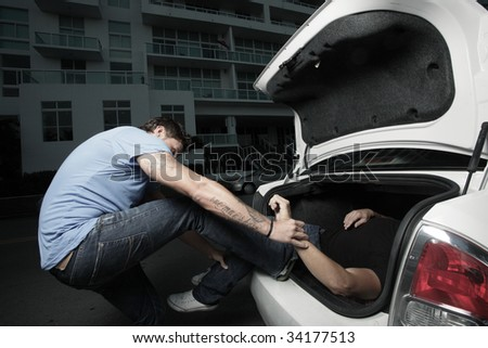 Man stuffing a dead body in the trunk - stock photo