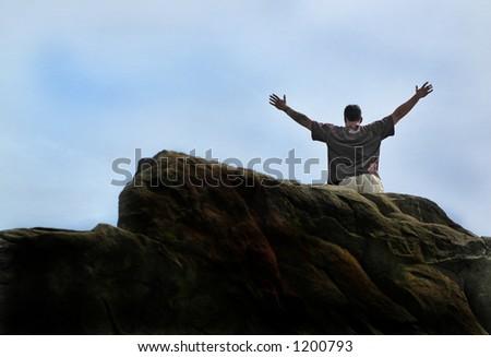 Man successfully climbs huge rock face - stock photo