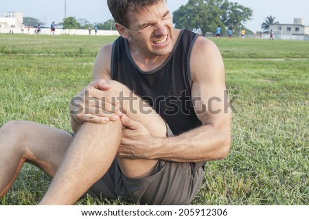 Man suffers painful hamstring injury and holds painful area with hands as he sits on grassy ball field - stock photo
