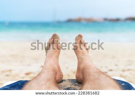 Man sunbathing on lounger. Legs.  - stock photo