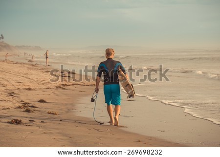 Man surfer walking along the beach with surfboard at sunset.  - stock photo