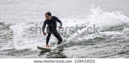 Man surfing a wave in the sea - stock photo