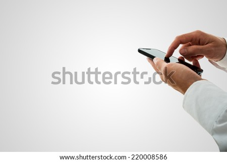 Man surfing the internet or making a call on a smartphone navigating the touchscreen with his finger over grey with copy space. - stock photo