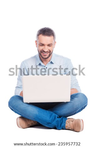 Man surfing the net. Handsome young man in casual wear sitting on the floor and working on laptop while being isolated on white background - stock photo