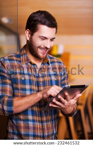 Man surfing the net. Handsome young man working on digital tablet and smiling while standing indoors - stock photo