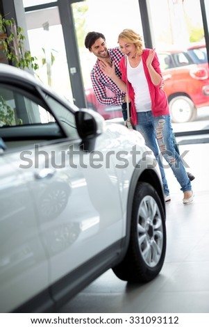 Man surprising his girlfriend with a new car, car dealership saloon - stock photo