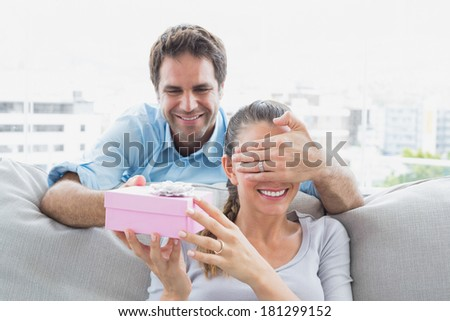 Man surprising his girlfriend with a pink gift on the sofa at home in the living room - stock photo