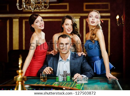 Man surrounded by ladies plays roulette at the casino - stock photo