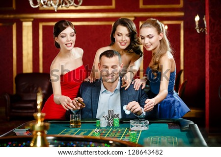 Man surrounded by women plays roulette at the casino - stock photo