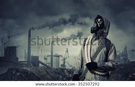 Man survivor in gas mask on industrial gray background - stock photo
