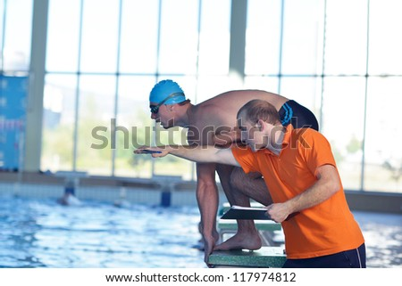 man swimmer practice jump in swimmpin pool with trainer - stock photo