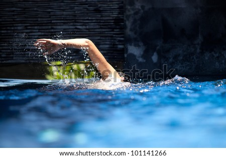 Man swimming crawl in private pool with splash arm - stock photo