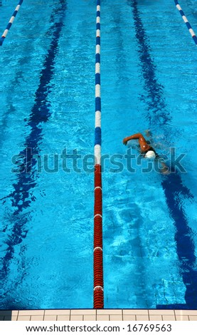 Man swimming in a pool lane seen from above - stock photo