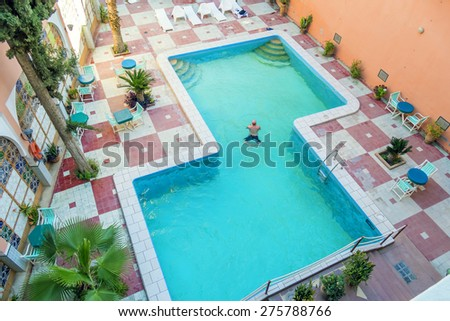Man swimming in hotel swimming pool - stock photo